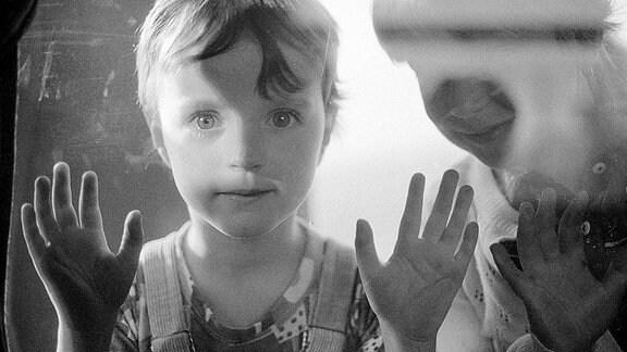 Ein Junge blickt durch ein Schaufenster in der DDR.
