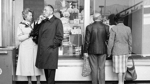 Menschen vor einem Schaufenster in der DDR.