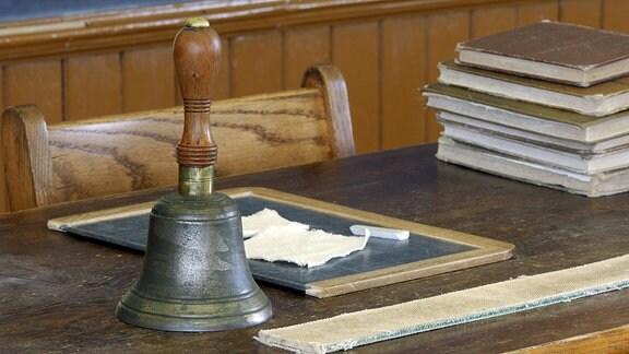 Lehrerpult aus den zwanziger Jahren mit Büchern, Schiefertafel, Kreide und einer Schulglocke