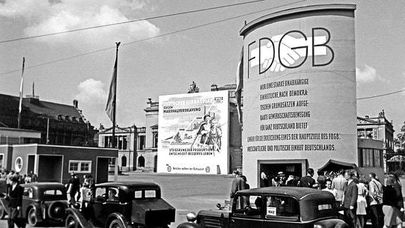 FDGB Plakat, Gewandhaus und Marktplatz in Leipzig. Passanten am Gewandhaus und Marktplatz.