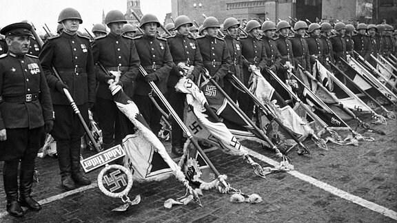 Sowjetische Soldaten mit gesenkten deutschen Truppenfahnen und Standarten bei der Siegesparade in Moskau