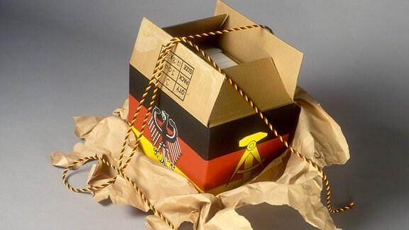 Wiedervereinigung - Aufgerissenes Paket mit den Landesfahnen von DDR und BRD, 1990
