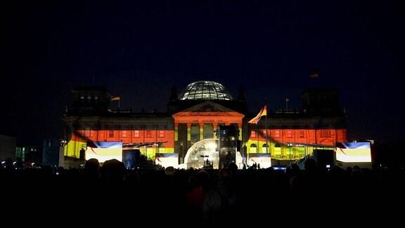 Lichtinstallation an der Fassade vom Reichstag in den Farben Schwarz-Rot-Gold beim Fest zum 20. Jahrestag der Deutschen Einheit vor dem Reichstag in Berlin.