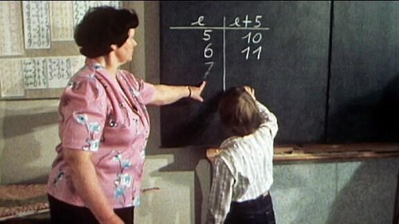 Lehrerin und Schulkind an der Tafel
