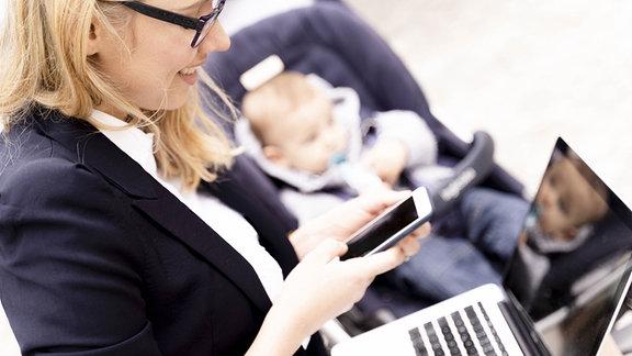 Symbolbild: Berufstätige Mutter im Büro