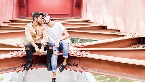 Junges schwules Paar sitzt auf Stahlträger einer Fußgängerbrücke