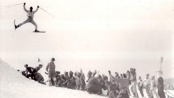 Skispringer springt über Menschenreihe.