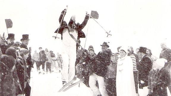 Skispringer zwischen vielen Menschen.