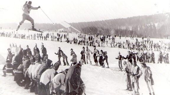 Ein Skispringer springt über eine Menschenreihe.
