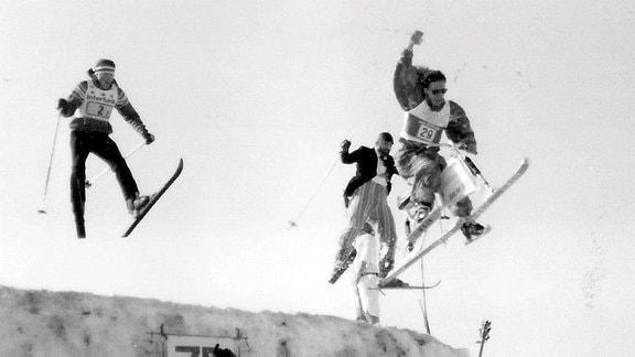 3 Skispringer springen über eine Schanze.