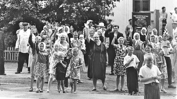 Frauen, Männer und Kinder stehen winkend vor einem Denkmal