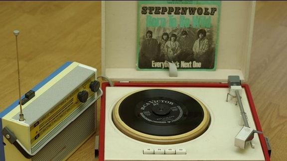 Kleiner Plattenspieler mit roter Verkleidung, darüber eine Schallplatte von Steppenwolf, daneben ein Transistorradio
