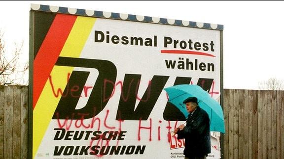 Ein Mann geht am 08.04.98 in Magdeburg an einem Wahlplakat der Deutschen Volksunion vorbei, das von Gegnern der Partei mit Farbe besprüht worden ist.