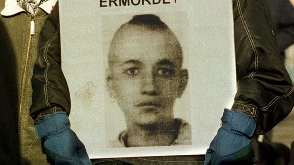 Ein Jugendlicher trägt am 08.02.1998 in Magdeburg bei einer Demonstration gegen rechte Gewalt ein Foto des vor einem Jahr von Skinheads ermordeten Punks Frank Böttcher.