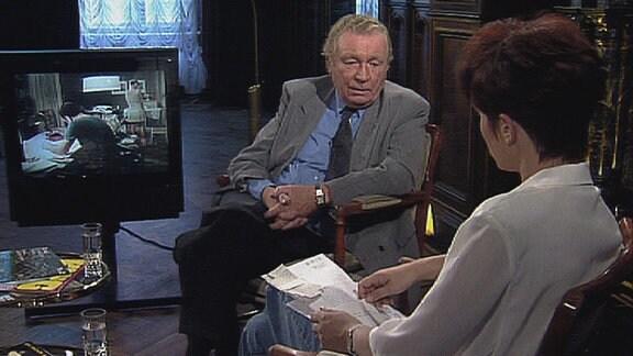 Frank Beyer im Sessel eines Kaminzimmers mit großem Fernsehbildschirm
