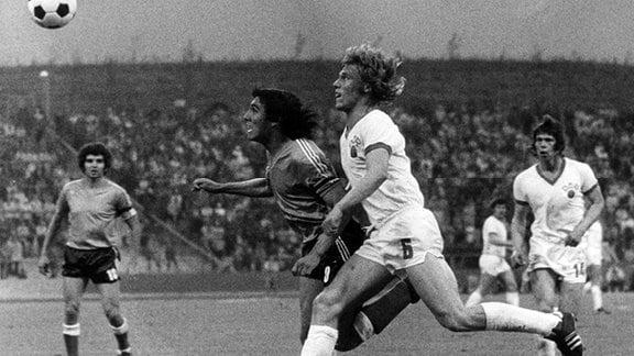DDR-Mittelfeldspieler Rüdiger Schnuphase (vorn, r) kämpft mit dem Argentinier Ramon Heredia (vorn,l) um den Ballbesitz. DDR-STürmer Jürgen Sparwasser (r, hinten) schaut zu. Die DDR-Elf trennt sich am 3.7.1974 im Gelsenkirchener Parkstadion im Gruppenspiel der 2. Finalrunde der Fußball-Weltmeisterschaft mit einem 1:1 von Argentinien.