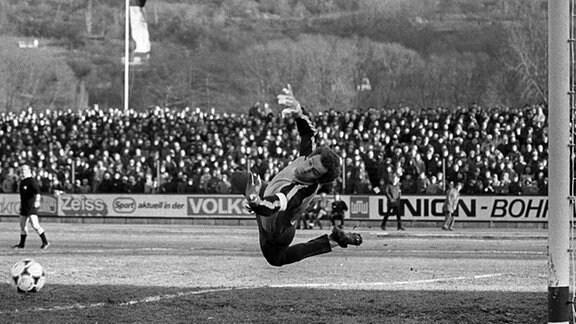 Der Erfurter Torhüter Wolfgang Benkert hechtet nach dem Ball am 14.11.1981 im Jenaer Ernst-Abbe-Sportfeld, wo sich im DDR-Fußballoberligaspiel der FC Carl Zeiss Jena und der FC  Rot-Weiß Erfurt (2:2) gegenüberstehen.