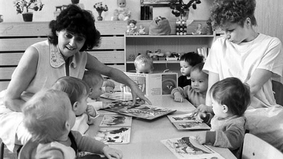 Erzieherinnen mit Kindern beim Anschauen von Bilderbüchern in einem Kinderheim in Zwickau, aufgenommen im Januar 1990.