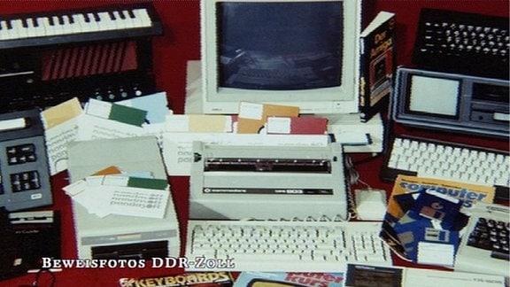 Foto des DDR-Zolls zeigt Sammlung beschlagnahmter Ware:  Schreibmaschinen, Disketten, Keyboard, PC-Bildschirm