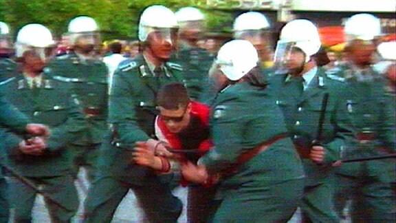 Volkspolizisten in grüner Monturr mit Helm halten Flüchtenden fest