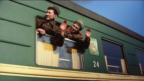Zwei Soldaten winken aus dem abfahrenden Zug.