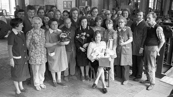 Eine Arbeiterin wurde ausgezeichnet und hält eine Urkunde und einen Präsentkorb in den Händen, die Brigade, das Kollektiv, steht rund um die Ausgezeichnete in einer Werkhalle im VEB Kabelwerk Oberspree (KWO), aufgenommen am 22.03.1977.