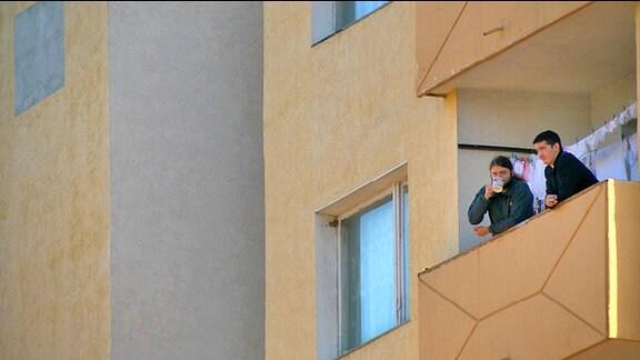 Nachaufnahme Plattenbau - zwei junge Männer auf einem Balkon