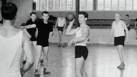 Alte Schwarzweißaufnahme: Handballer in einer Turnhalle