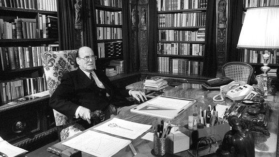 Ein Mann mit Brille auf einem geblümten Sessel vor eienr Bücherwand. Vor ihm ein großer Schreibtisch.