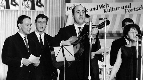"""Manfred Krug (M., mit Gitarre) und Ruth Hohmann (r) beim Auftritt der """"Jazz-Optimisten"""" am 31.10.1965 in der Kongresshalle am Berliner Alexanderplatz."""