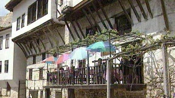 Eine Terasse mit Sonnenschirmen an einem Haus