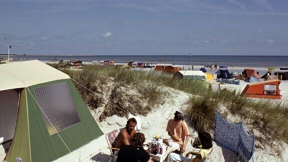 Urlauber sitzen vor ihrem in den Dünen aufgebauten Zelt und lassen sich eine Mahlzeit schmecken, aufgenommen im Sommer 1990 im Ostseebad Prerow.