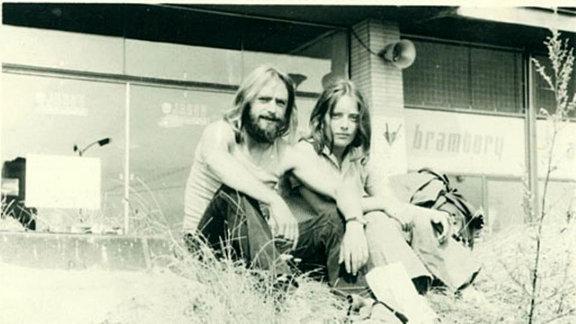 Ein junges Paar sitz im Gras vorm Haus.