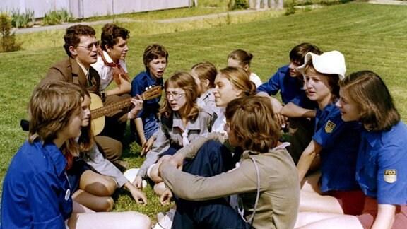 """Im Zentralen Pionierlager """"Rudi Arndt"""" Oybin im Zittauer Gebirge verbrigen Jugendliche aus der UdSSR, der VR Polen und Bulgarien zusammen mit Teilnehmern aus der CSSR und der DDR frohe Ferientage, sie sitzen zusammen und singen zur Gitarre."""