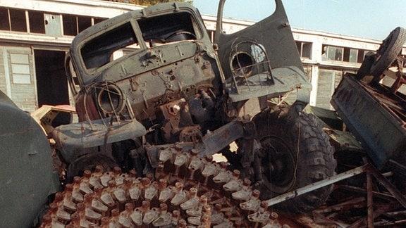 Militärschrott, wie alte Panzerketten und ausrangierte Lastwagen, stapeln sich neben dem sojetischen Kasernenkomplex in Neu-Fahrland bei Berlin