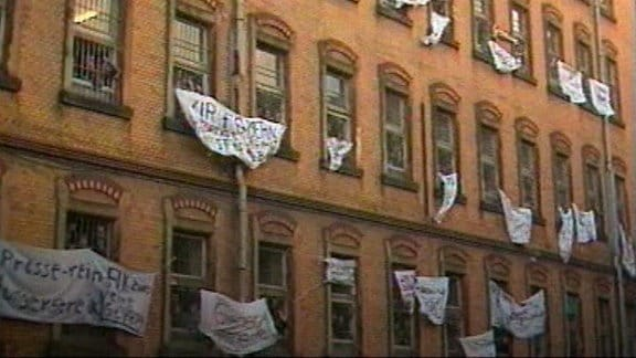 Häftlinge protestieren im Dezember 1989 mit beschriebenen Bettlaken
