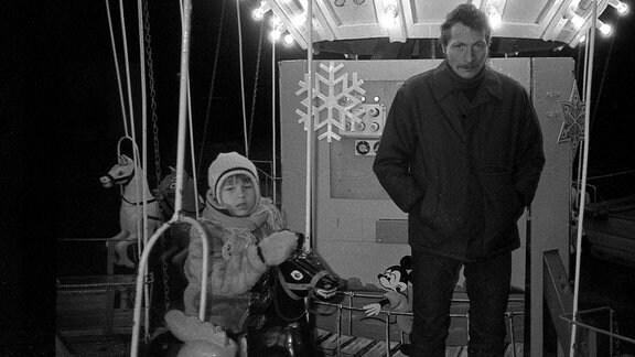 Kind und Mann auf einem Karussell auf dem Leipziger Weihnachtsmarkt in 1980er-Jahren
