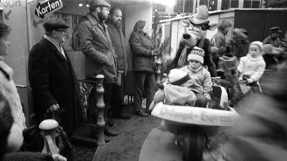 Kinder fahren Karrussel in den 80-er Jahren auf dem leipziger Weihnachtsmarkt.