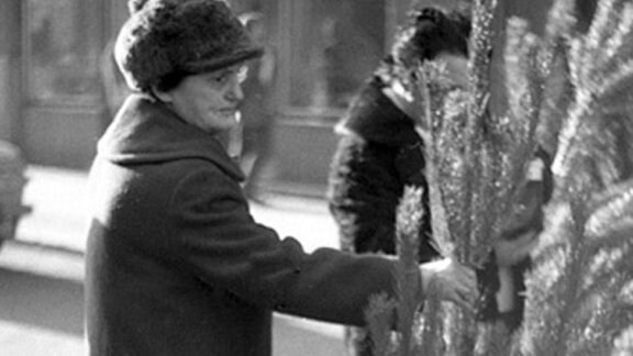 Alte Frau hält Tannenbaum in den 80-er Jahren in Leipzig.