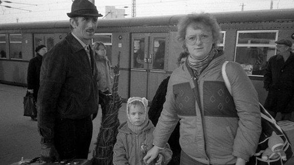Familie mit eingewickelten Tannenbaum steht auf Bahnhof vor Zug in den 80-er Jahren in Leipzig.