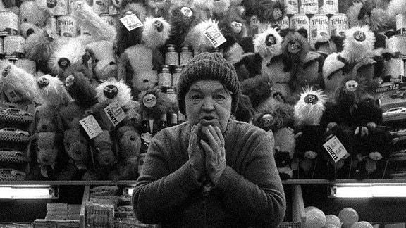 Alte Frau vor Losbude mit vielen Plüschtieren in den 80-er Jahren in Leipzig