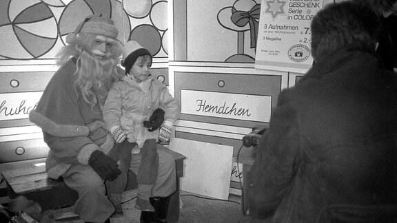 Kleiner Junge sitzt auf dem Schoß des Weihnachtsmann in den 80-er Jahren auf dem Leipziger Weihnachtsmann