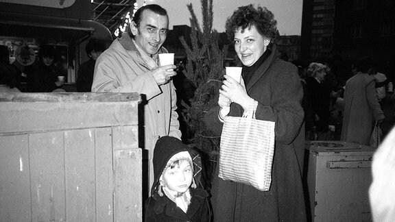 Familie in der 80er-Jahren mit Glühwein auf dem Weihnachtsmarkt