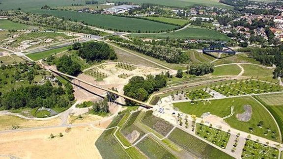 Vogelperspektive Blick auf Landschaft mit Wiesen, Wegen, Hügeln und Dorf im Hintergrund