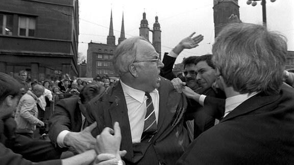 Nachdem Bundeskanzler Helmut Kohl am 10. Mai 1991 vor dem Stadthaus in Halle von einem Demonstranten mit Eiern beworfen worden ist, versucht der in Wut geratene Kanzler sich mit eibeschmierter Jacke einen Weg durch die ihm ansonsten zujubelnde Menge zu bahnen, um den Täter ausfindig zu machen.