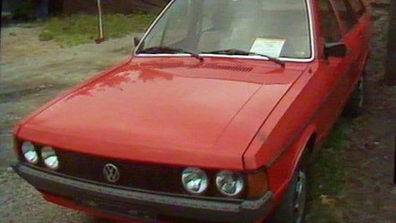 Vor einem Privatgrundstück steht ein alter, roter VW Passat mit einem Verkaufsschild hinter der Frontscheibe.