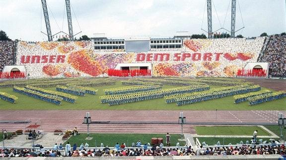 Während der Darbietungen der Turnerinnen und Turner auf dem Rasen formen Tausende von Sportlern auf den Rängen Losungen wie hier gerade ''Unser Herz dem Sport''.