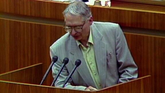Jens Reich steht vor dem Rednerpult und spricht bei der 30. Volkskammertagung