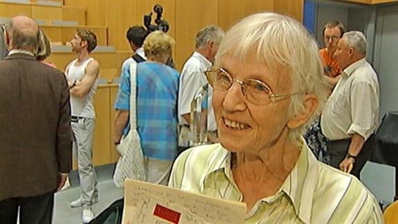 Eine Seniorin in einem Hörsaal