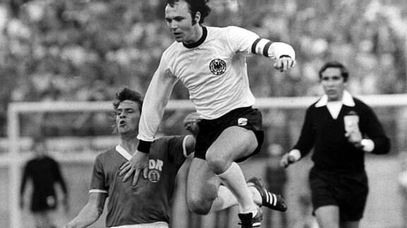 Libero Franz Beckenbauer (oben) überspringt in fairer Haltung den am Boden liegenden DDR-Abwehrspieler Konrad Weise (unten).